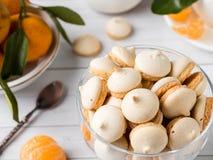 La meringue de biscuits en mandarines d'un vase en verre avec le vert part dans un plat sur le fond blanc Image stock