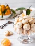 La meringue de biscuits en mandarines d'un vase en verre avec le vert part dans un plat sur le fond blanc Image libre de droits