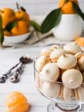 La meringue de biscuits en mandarines d'un vase en verre avec le vert part dans un plat sur le fond blanc Photo stock