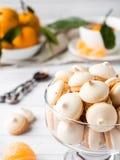 La meringue de biscuits en mandarines d'un vase en verre avec le vert part dans un plat sur le fond blanc Photographie stock