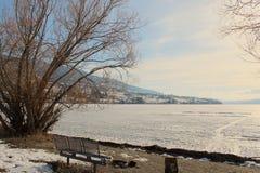 La mesa de picnic y el fuego marcan con hoyos en línea de la orilla de lago congelado Fotos de archivo libres de regalías