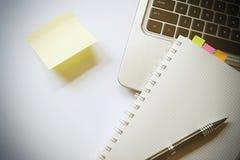 La mesa hace que el post-it de la pluma del ordenador portátil para añada el texto y el cuaderno tiene espacio de la copia y colo Foto de archivo
