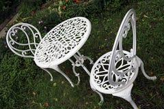 La mesa redonda y las sillas del metal blanco fijaron en el jardín imagenes de archivo