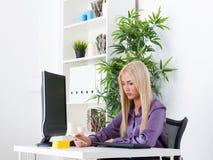 La messagerie textuelle décontractée de femme d'affaires dans le bureau lumineux Photos libres de droits
