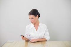 La messagerie textuelle d'une chevelure brune calme de femme d'affaires Photo stock
