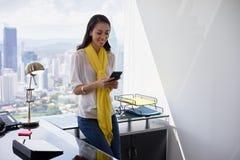 La messagerie textuelle de femme d'affaires au téléphone dans le bureau 3 Image libre de droits