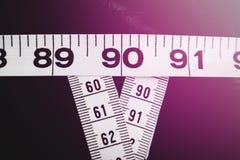 La mesure attache du ruban adhésif à montrer 90-60-90 en tant que paramètres idéaux pour des femmes Photos stock