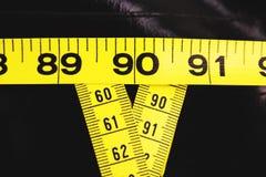 La mesure attache du ruban adhésif à montrer 90-60-90 en tant que paramètres idéaux pour des femmes Images stock