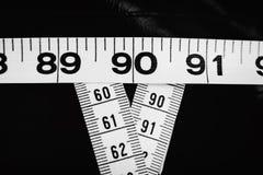 La mesure attache du ruban adhésif à montrer 90-60-90 en tant que paramètres idéaux pour des femmes Photo stock