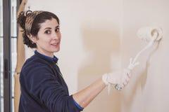La metà di donna adulta dipinge le stanze delle sue stanze della casa fotografie stock