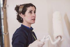 La metà di donna adulta dipinge le stanze delle sue stanze della casa fotografie stock libere da diritti