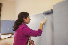 La metà di donna adulta dipinge le stanze delle sue stanze della casa immagini stock