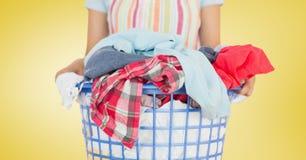 La metà di sezione del canestro di lavanderia femminile della tenuta del pulitore ha riempito di abbigliamento Immagine Stock Libera da Diritti