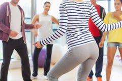 La metà di sezione della classe di forma fisica e l'istruttore che fa i pilates si esercitano Immagine Stock Libera da Diritti