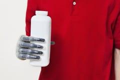 La metà di sezione di una bottiglia della tenuta dell'uomo con prostetico consegna il fondo grigio Fotografie Stock