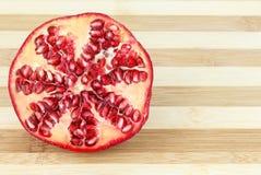 La metà ha affettato i semi della frutta del melograno su un bordo di legno fotografia stock