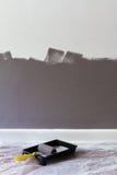 La metà ha dipinto la parete con il rullo ed il vassoio con spazio per testo fotografia stock libera da diritti