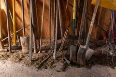 La metà inferiore di una selezione degli strumenti di giardinaggio compreso la vanga, la forcella, la mazza ed il rastrello dent fotografia stock