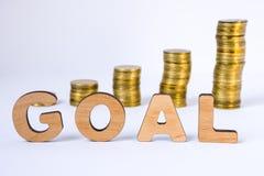 La meta de la palabra de letras tridimensionales está en primero plano con las columnas del crecimiento de monedas en fondo borro Imagen de archivo libre de regalías