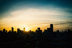 La metrópoli es llena de edificios altos en la puesta del sol en el horizo Fotos de archivo libres de regalías