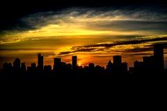 La metrópoli es llena de edificios altos en la puesta del sol en el horizo Foto de archivo
