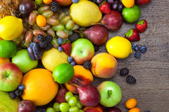 La mezcla de frutas coloridas con agua cae en fondo de madera Imágenes de archivo libres de regalías