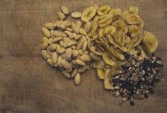 La mezcla de rebanadas del plátano, de habas del chocolate y de almendras secadas Foto de archivo