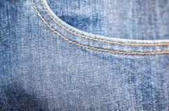 La mezclilla azul del dril de algodón azul stictched el fondo del bolsillo - borroso fotografía de archivo