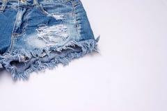 la mezclilla corta en el fondo blanco, ropa del verano de la mujer viaja imagen de archivo