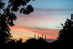 La mezquita se coloca firmemente detrás de la puesta del sol Imagen de archivo