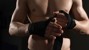 La mi section en gros plan d'un homme musculaire sans chemise lie le bandage sur sa main banque de vidéos