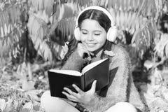 La mia storia di autunno Piccolo bambino ascolta il libro elettronico in cuffie Poco bambino gode di di imparare nel parco di aut immagini stock