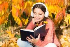 La mia storia di autunno Piccolo bambino ascolta il libro elettronico in cuffie Poco bambino gode di di imparare nel parco di aut fotografie stock