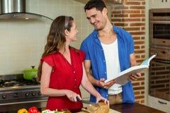 La miche de pain et l'homme de coupe de femme vérifiant la recette réservent Image libre de droits