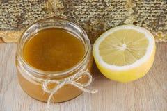La miel de oro en el peine en un tarro y un amarillo cortó el limón Imagenes de archivo