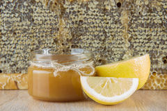La miel de oro en el peine en un tarro y un amarillo cortó el limón Imagen de archivo
