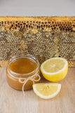La miel de oro en el peine en un tarro y un amarillo cortó el limón Fotos de archivo