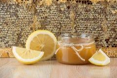 La miel de oro en el peine en un tarro y un amarillo cortó el limón Fotos de archivo libres de regalías