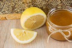La miel de oro en el peine en un tarro y un amarillo cortó el limón Imagen de archivo libre de regalías