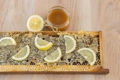 La miel de oro en el peine en un tarro y un amarillo cortó el limón Fotografía de archivo libre de regalías