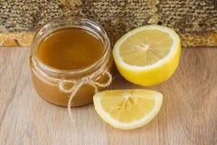 La miel de oro en el peine en un tarro y un amarillo cortó el limón Imágenes de archivo libres de regalías
