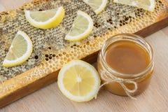 La miel de oro en el peine en un tarro y un amarillo cortó el limón Foto de archivo