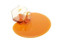 La miel desborda un tarro de cristal Foto de archivo libre de regalías