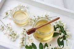 La miel dulce con el acacia florece en bandeja de madera Foto de archivo
