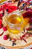 La miel dulce en pote con el arco en un fondo de madera adornó las hojas y la frambuesa de otoño Foto de archivo libre de regalías