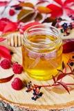 La miel dulce en pote con el arco en un fondo de madera adornó las hojas y la frambuesa de otoño Imágenes de archivo libres de regalías