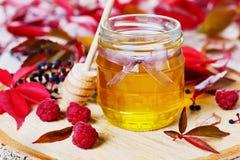 La miel dulce en pote con el arco en un fondo de madera adornó las hojas y la frambuesa de otoño Imagen de archivo