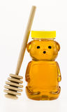 La miel en un envase de plástico formó como un oso con una piedra de afilar de madera Fotos de archivo libres de regalías