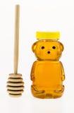 La miel en un envase de plástico formó como un oso con una piedra de afilar de madera Fotografía de archivo