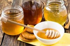 La miel en un vidrio sacude en un fondo rústico de madera Fotos de archivo